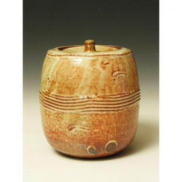 PR 389  A Lidded jar with a shino glaze.